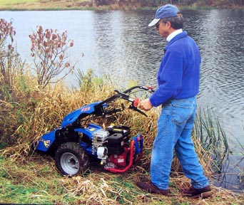 Man using BCS gardening equipment.  He is using the BCS tractor with sicklebar mower attachment for his lawn and garden needs. These BCS two wheel tractors have interchangeable attachemnts that make them a cultivator, brush mower, snowthrower, dozer, sicklebar mower, lawn mower, sweeper and chipper/shredder.